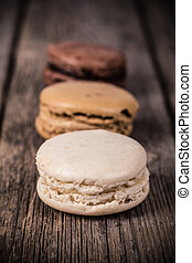 Assorted macaroons over old wood background. Vintage effect processing with intentional vignetting