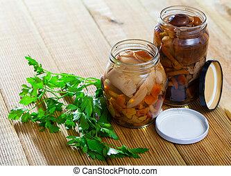 Assorted marinated mushrooms in glass jar