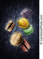 Assorted multi flavoured macaroons floating and exploding against black background