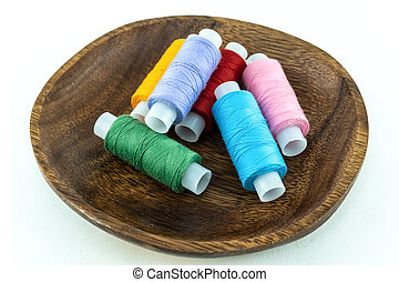 assorted multicolored threads skein of green, blue and pink folded in a wooden bowl