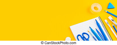 Assorted office and school white and blue stationery on yellow
