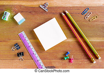 Assorted Office Supplies on Wooden Table, Emphasizing White Blank Notepad at the Center with Copy Space for Texts.