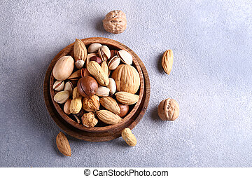 assorted organic nuts in a wooden bowl