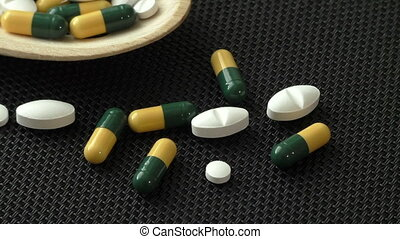 Assorted pharmaceutical medicine pills, tablets and capsules on wooden spoon