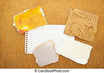 assorted pieces of ripped scrap paper, on grunge background