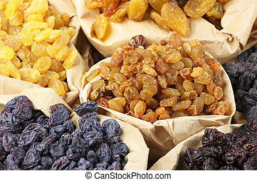 Various raisins in paper bags. Full frame.