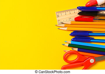 Assorted school supplies on a yellow background