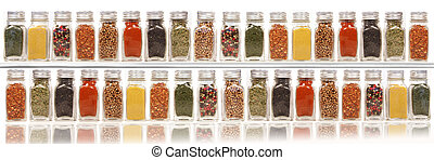Assorted spices on two layer shelves against white ...