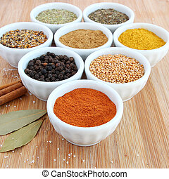 Various spices and herbs - cumin, paprika, mustard seeds, paprika, rosemary, Montreal steak spice, basil, curry and black pepper - in small white bowls