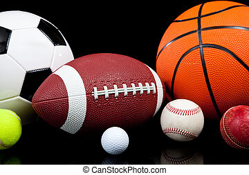 Assorted sports balls on a black background - Assorted...