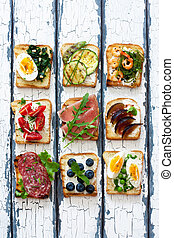 Assorted toasts with eggs, ham ,vegetables and fruits served on a white wood background