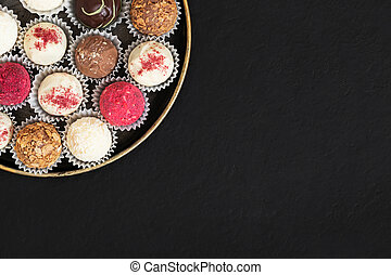 Assorted truffles in a plate on a black background. Homemade candies or energy balls with dried fruits and chocolate. Superfood. Copy space, top view, flat lay.