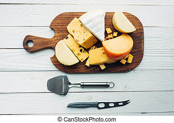 assorted types of cheese and cutlery