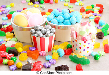 Assorted variety of sweet sugar candies includes bonbons, gummy bears, gum balls and sugar fruit slices.
