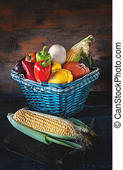 Assorted vegetables, pumpkins, zucchini, cucumbers, tomatoes, garlic, corn , pepper harvest in a beautiful wicker basket. Thanksgiving.