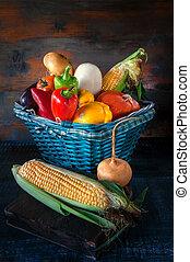Assorted vegetables, pumpkins, zucchini, cucumbers, tomatoes, turnips, garlic, corn, pepper gather in a beautiful wicker basket. Thanksgiving.