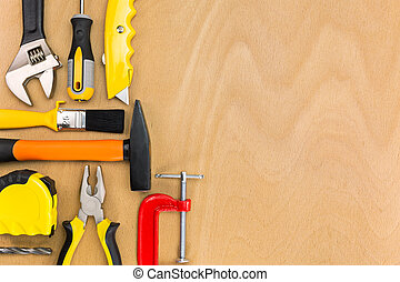 Assorted work tools on wooden background