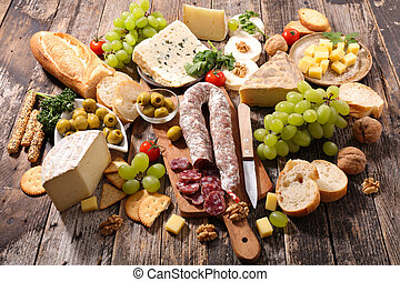 assortement of cheese with grape, bread, and salami