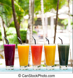 Assortment juices, smoothies, beverages, drinks variety on a outdoor tropical background Copy space