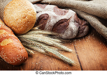 baked bread - assortment of baked bread on wood table