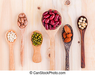 Assortment of beans and lentils in wooden spoon on wooden ...