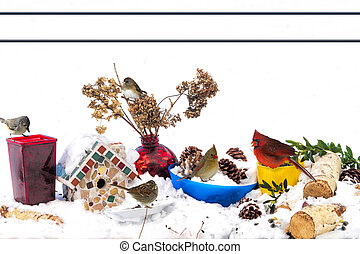 Assortment of Birds Feeding out of colorful container after snowstorm