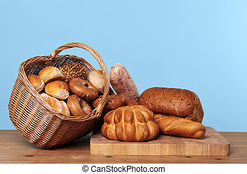 Photo of various types of bread loaves and rolls in a wicker basket on a wooden table with blue background.
