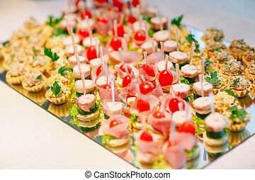 Assortment of canapes with fresh vegetables and salad. Banquet service.