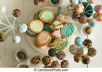 Assortment of candies, cake pops and cookies on wooden table...