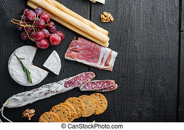 Assortment of cheese and meat appetizers, on black wooden table, top view with copy space for text