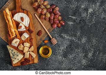 Assortment of cheese with honey, nuts and grape on a cutting board.