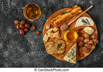 Assortment of cheese with wine, honey, nuts and grape on a cutting board.