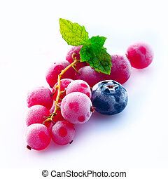 Assortment of chilled redcurrant, blueberry and raspberry berries with skins frosted with moisture