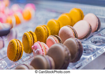 Assortment of colorful macarons cakes for sale on counter of candy shop