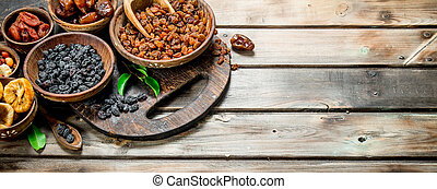 Assortment of different dried fruits in bowls. On a Wooden background.