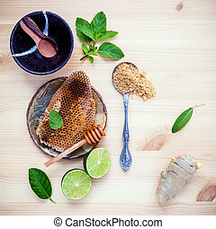 Assortment of dried herbs and fresh herbs tea. Honeycomb in ceramic plate with Fresh herbs peppermint , sage ,lime slice ,ginger powder and ginger root set up on wooden background.