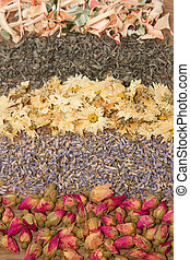 Assortment of dried tea in wooden background