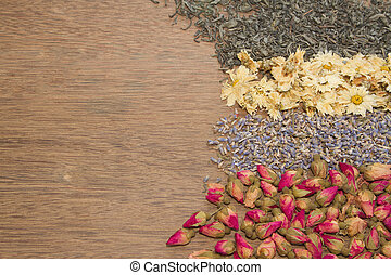 Assortment of dried tea on wooden background