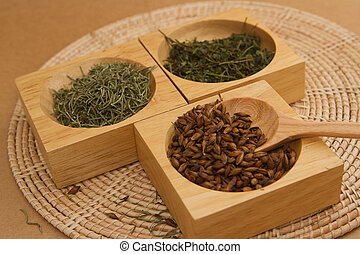 Assortment of dry tea in bowl on wqqden background