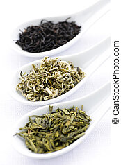 Black, white and green dry tea leaves in spoons