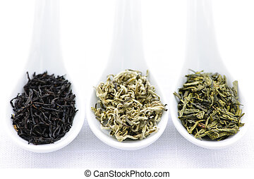 Assortment of dry tea leaves in spoons - Black, white and...