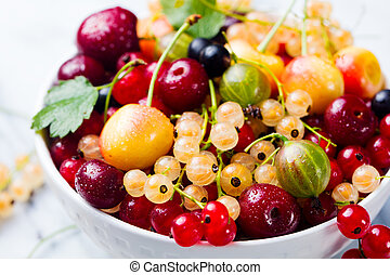 Assortment of fresh berries in white bowl.