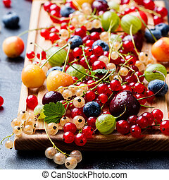 Assortment of fresh berries. Wooden cutting board