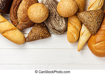 Assortment of fresh bread on a white wooden background. top view with copy space