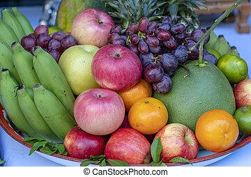 Assortment of fresh fruit banana, grapes, orange, apple, pineapple, tangerine and grapefruit on a tray. Closeup