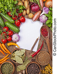 Assortment of fresh vegetables and blank recipe book on a ...