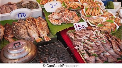 Variety of grilled seafoods, including squid, tilapia, crabs and prawns, displayed for sale at an outdoor public market in Asia. DCI 4k video