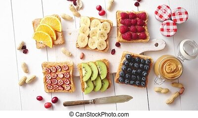Assortment of healthy fresh breakfast toasts. Bread slices with peanut butter and various fruits and ingredients on side. Placed on white wooden table. Top view, with copy space.