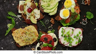 Assortment of home made sandwiches with various toppings. ...