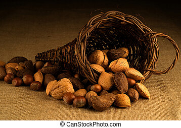 Assortment of nuts in basket on hesian background - An...